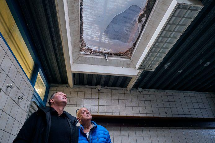Bestuurslid André van Dijk (links) en Rob Hasselmeijer van de kantinecommissie bekijken het lekkende dak in een kleedkamer op sportpark De Lockhorst, eind 2019.