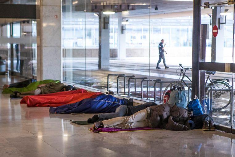 ► Pendelaars zijn het beeld intussen gewend: vele tientallen vluchtelingen die in het Noordstation liggen te slapen. Beeld Jan De Meuleneir - Photo News