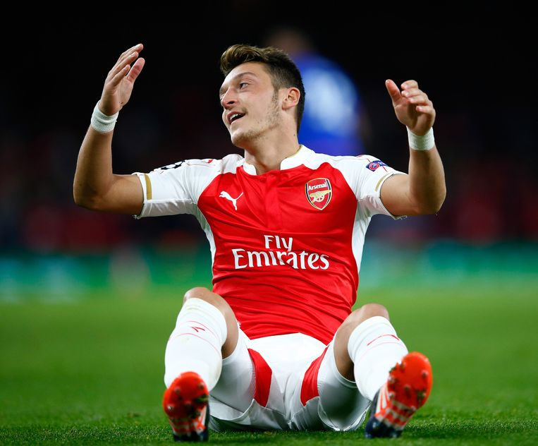 Arsenal-speler Özil zit balend op de grond. Beeld getty