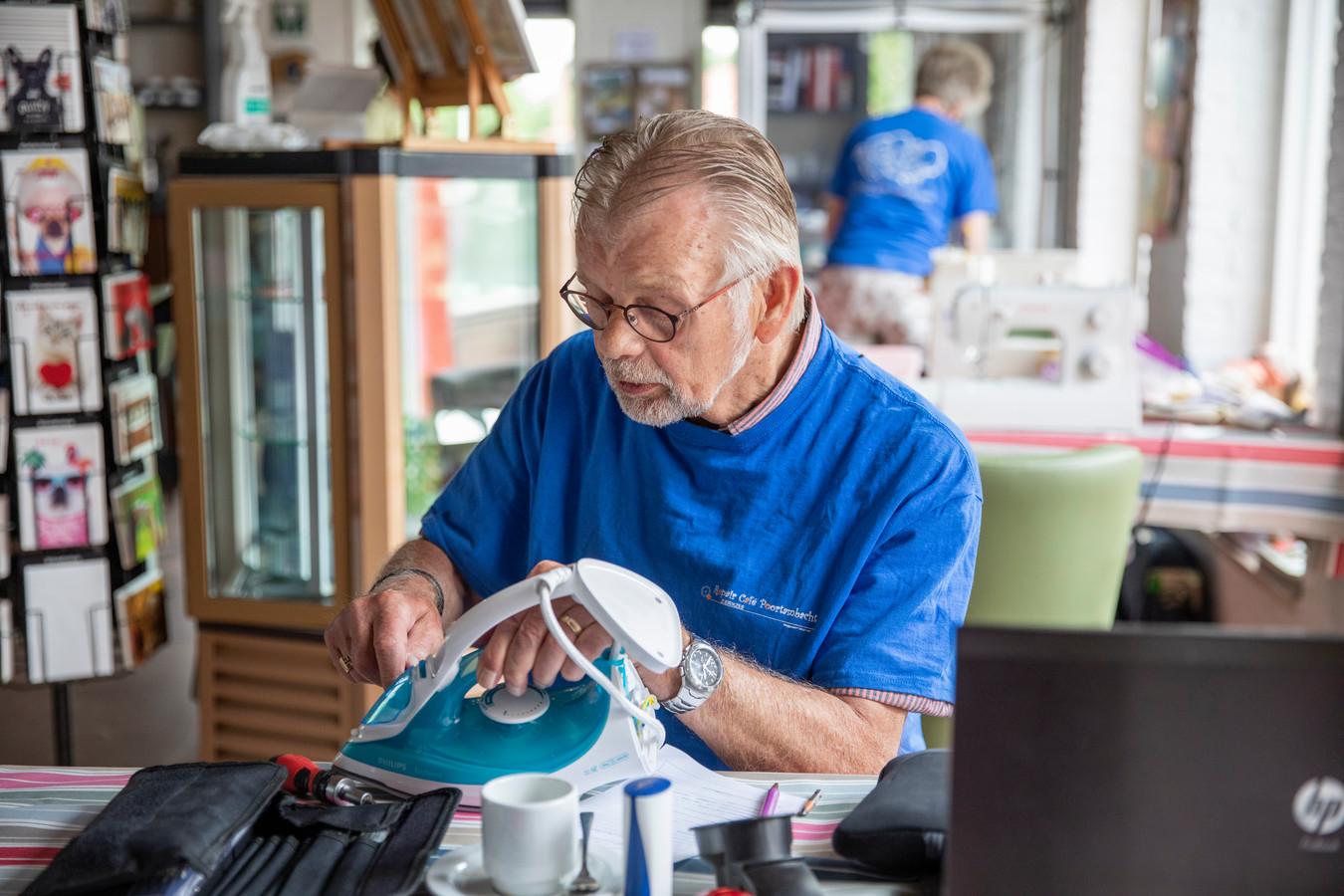 Willem Rapati buigt zich over het strijkijzer van mevrouw Schaap uit Zierikzee.