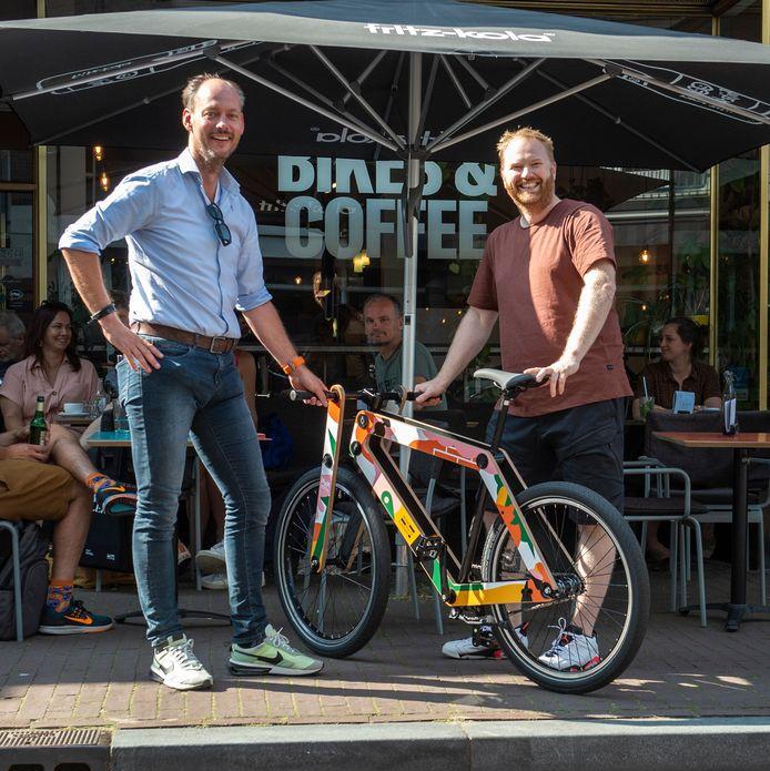 Wethouder Daan Quaars (l) heeft nieuwe Blind Walls-fietsroute overhandigd aan Dennis Elbers (r).