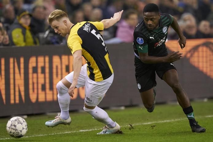 Max Clark duelleert namens Vitesse met Deyovaisio Zeefuik van FC Groningen. Hij trekt het gras van GelreDome zichtbaar mee.