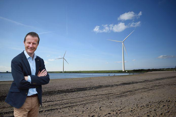 Wethouder Peter Schop met op de achtergrond een artist's impression van de windmolens bij de Haringvlietdam.