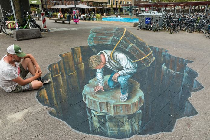 Straatkunstenaar Leon Keer bij zijn 3D-tekening op het Willemsplein, waar de HBS heeft gestaan. De man in het gat verwijst naar de evacuatie. Op de achtergrond het wederopbouwmonument de AKU-fontein.