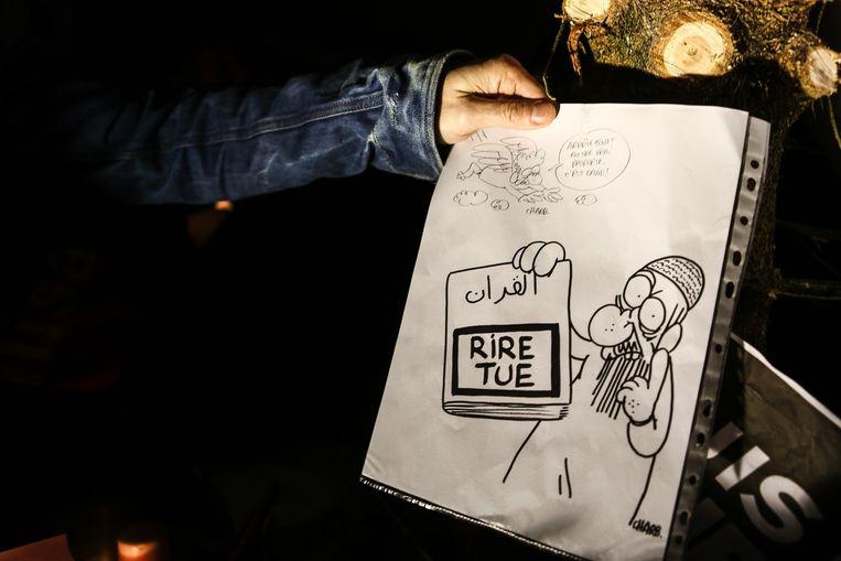 Een man houdt een Charlie Hebdo-illustratie vast, Luxemburg Beeld Belga