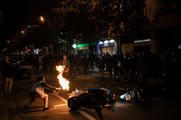 Een betoger steekt een motorfiets van de politie in brand tijdens het protest tegen de opsluiting van een Catalaanse rapper.