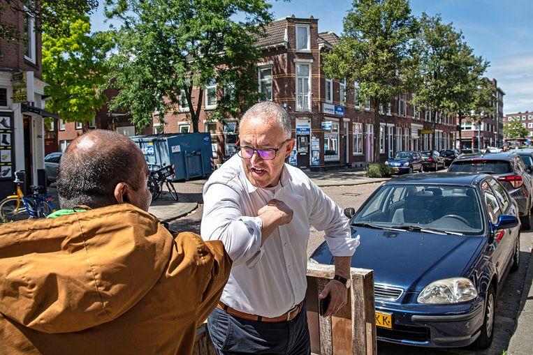 Aboutaleb groet een wijkbewoner.  Beeld Guus Dubbelman / de Volkskrant