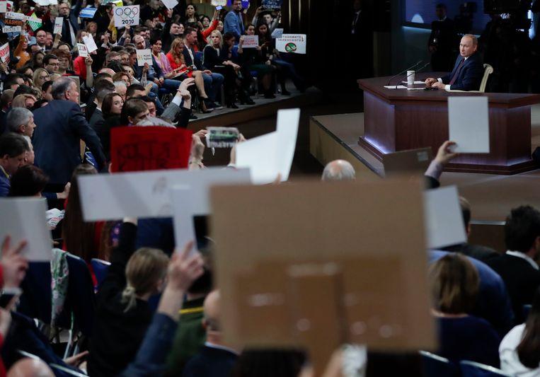 Tijdens de jaarlijkse persconferentie van Poetin proberen verslaggevers met knuffels en spandoeken zijn aandacht te trekken. Beeld AP