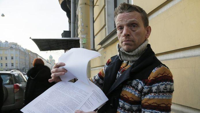 Greenpeace-acticist Mannes Ubels laat journalisten zijn papieren zien voor het immigratiekantoor in St. Petersburg