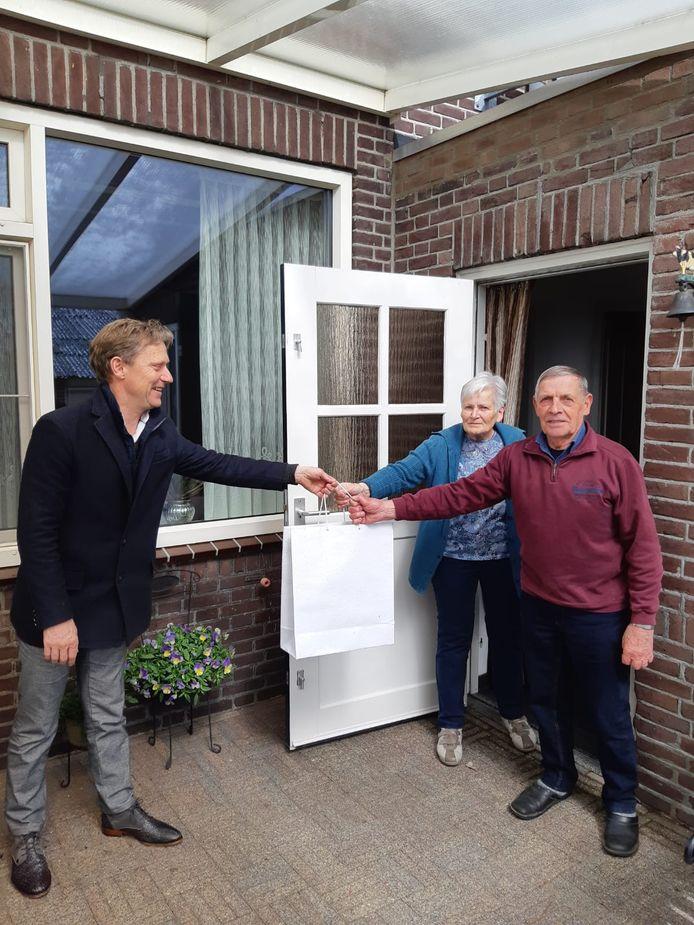 Wethouder Mathijs Kuijken reikt een presentje uit aan het paar Theuws in 't Loo.
