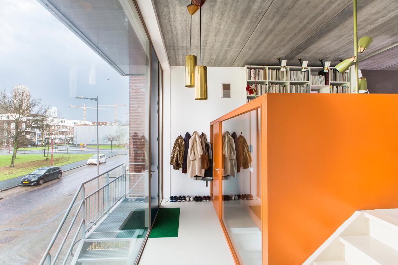 'We hebben de deur naar het atelier en het blok daaromheen oranje gemaakt omdat we dat mooi vonden contrasteren met de donkerblauwe voordeur. Het is bewust een soort object, een kleurrijk statement in de verder vrij witte ruimte.'