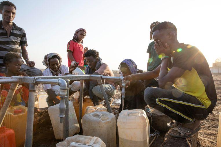 Tigrese vluchtelingen vullen hun jerrycans met water. Nyssen: 'Voedsel is een wapen in deze burgeroorlog.'  Beeld AP