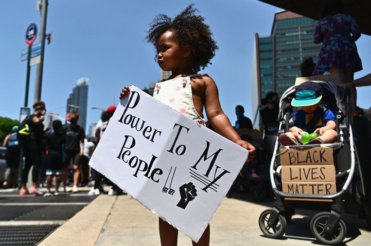Een meisje loopt mee in een Black Lives Matter-protestmars in Brooklyn, New York. Beeld AFP