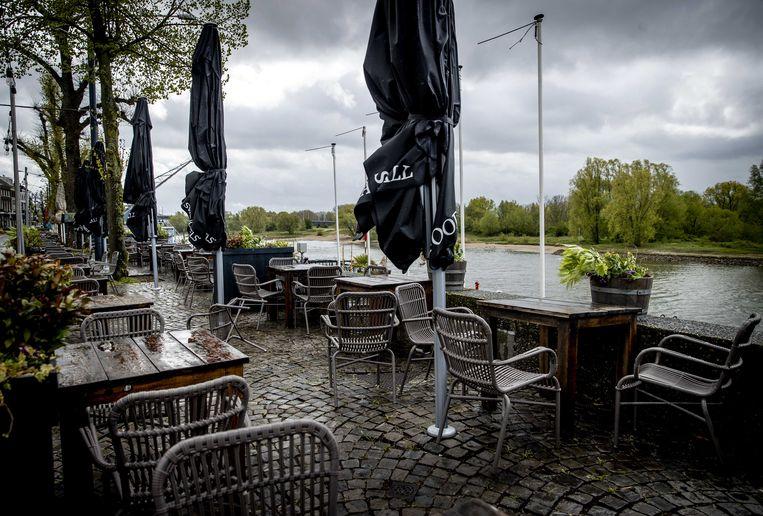 Een leeg terras op een druilerige dag in het centrum van Arnhem. Niet alleen slecht weer is een bedreiging voor de restaurants, ook door corona verandert het consumentengedrag. Beeld