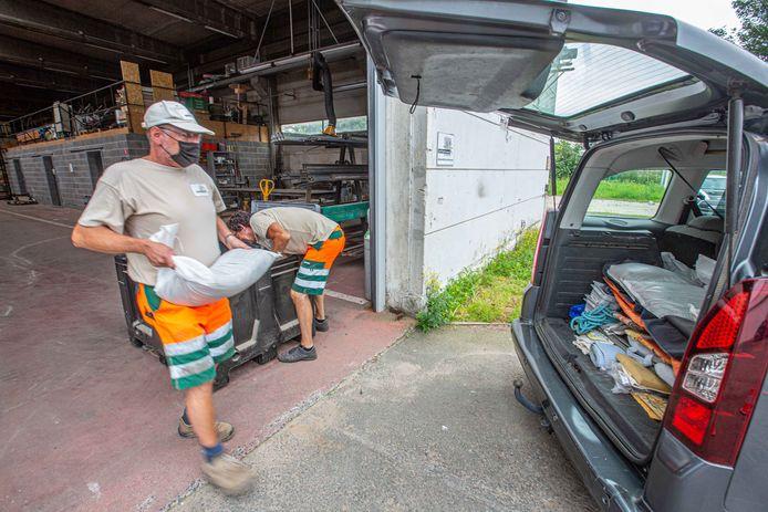 Enkele werklieden laden de auto van Luc Van Onsem met zandzakjes.