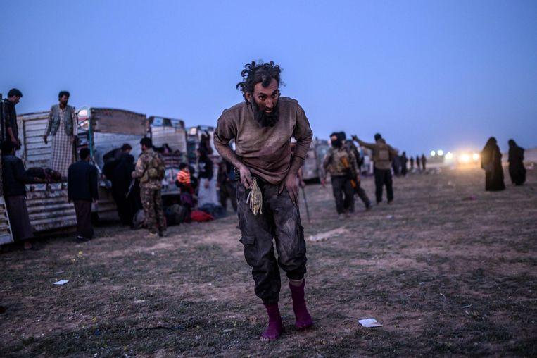 Een vermoedelijk lid van Islamitishe Staat wandelt voorbij leden van de SDF na het verlaten van Baghouz.  Beeld AFP