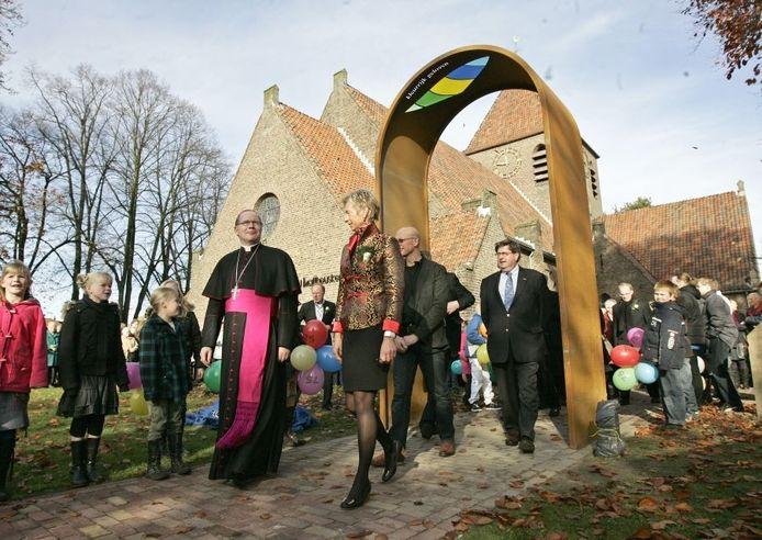 Aartsbisschop Wim Eijk, vice-voorzitter Marian Bolster van het kerkbestuur, kunstenaar Anton ter Braak en burgemeester Hein Bloemen lopen als eerste onder het net onthulde kunstwerk door. Foto: Jan Houwers
