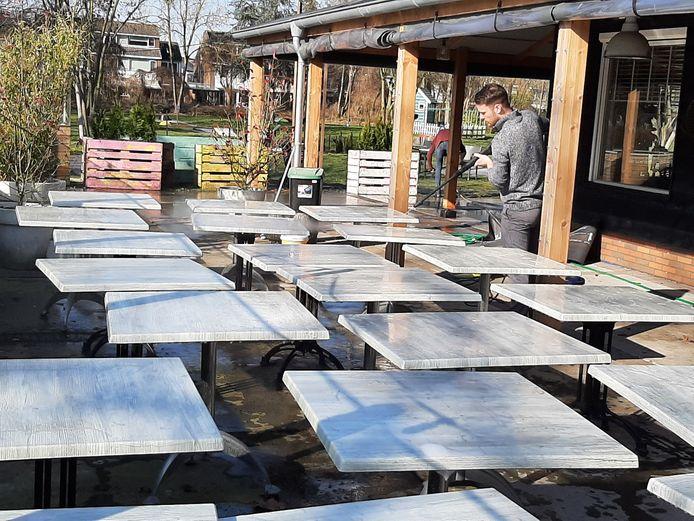 Een medewerker van Bij Hen maakt met de hogedrukspuit de terrastafels schoon.