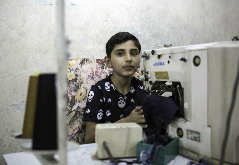 Hamza naait tien uur per dag aan spijkerbroeken voor kinderen in Gaziantep, Turkije Beeld Hollandse Hoogte