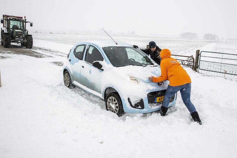 Een boer schiet een automobilist te hulp die met zijn auto een sneeuwduin is ingereden. Beeld ANP