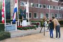 Jochem van de Wiel en zijn 9-jarige zoon Beau kijken naar de bloemen die op 4 mei overdag al bij het Oisterwijkse oorlogsmonument Gevleugelde Vrijheid zijn neergelegd.