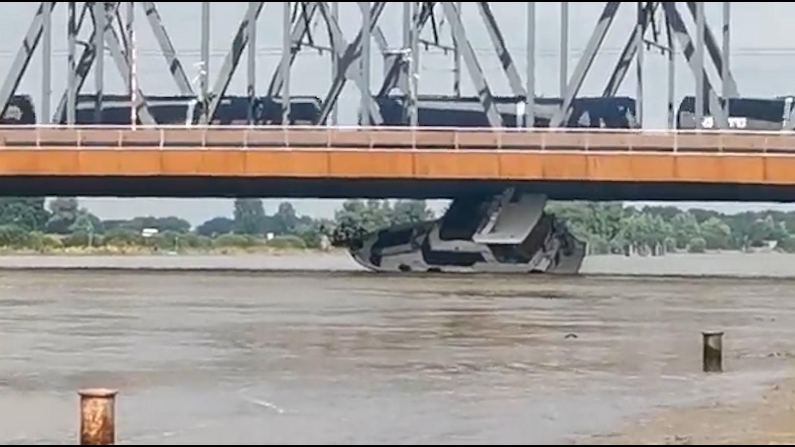 Un yacht de plaisance sous un pont.