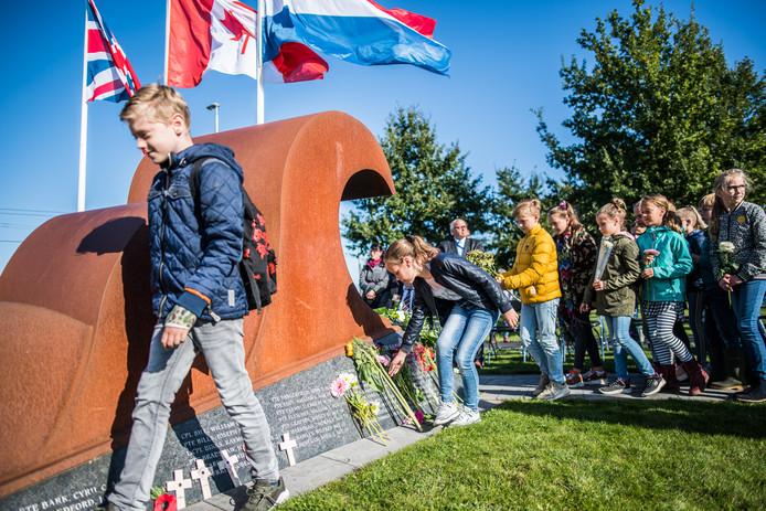 Leerlingen van basisschool Confetti leggen bloemen neer bij monument 'De Golf' voor de gesneuvelden van het Wiltshire Regiment.