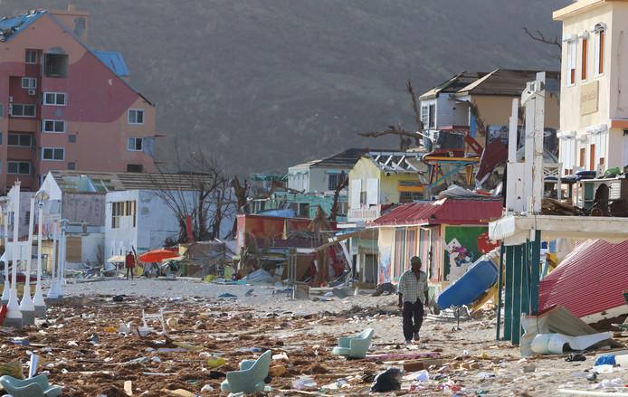 Een man loopt door een van de verwoeste straten op Sint-Maarten.