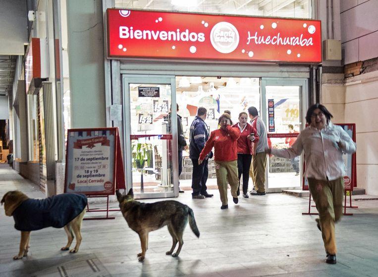 Mensen rennen in paniek een winkel in Santiago uit. Beeld afp