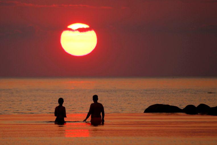 Mensen voor de kust van Salacgriva in Letland.  Beeld EPA