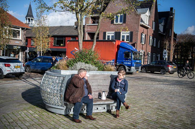 Medewerkers van de provincie Overijssel drinken een kopje koffie buiten op een bankje in Tubbergen, waar alles dicht is.  Beeld Koen Verheijden