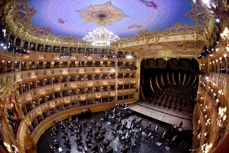 De opera van Venetië opende eergisteren heel voorzichtig het post-corona-seizoen met de voorstelling Verdi e la Fenice. Het publiek was alleen in de loges welkom, het orkest nam de vloer in, de zangers zaten op het podium. Ook de bars, restaurants en bisocopen zijn weer open in het zwaar getroffen Italië.  Beeld AFP