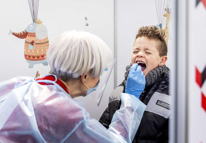 Een kind ondergaat een coronatest in een speciale kindertestbalie. Speciaal voor kinderen wordt een flexibeler wattenstaafje gebruikt, waardoor de test minder pijnlijk is en minder diep de neus en keel in hoeft.