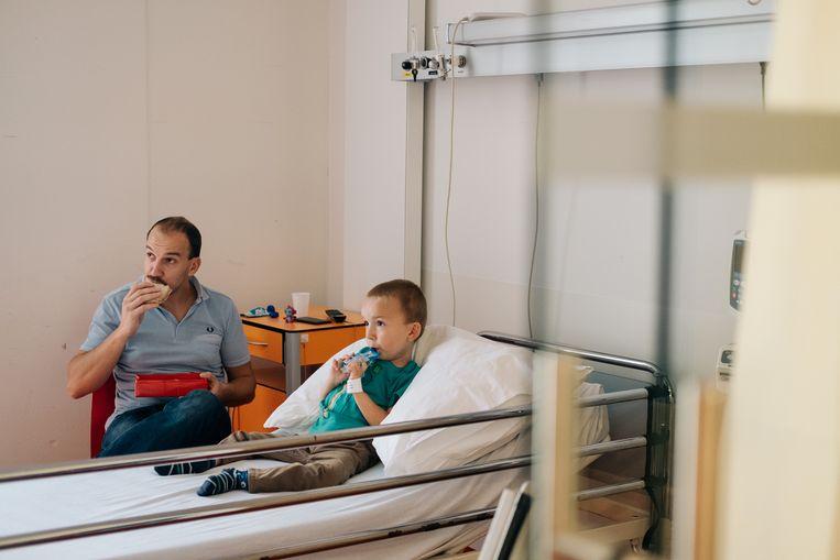Vader en zoon kijken geboeid naar tv in Tuurs vertrouwde kamer in het UZ Gent. Beeld Wouter Van Vooren