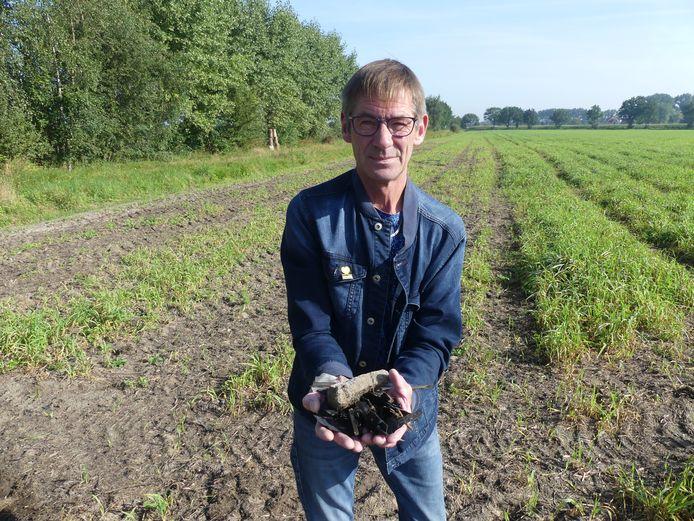 Luc Roggeman toont enkele stukken plastic die verspreid liggen over het terrein.