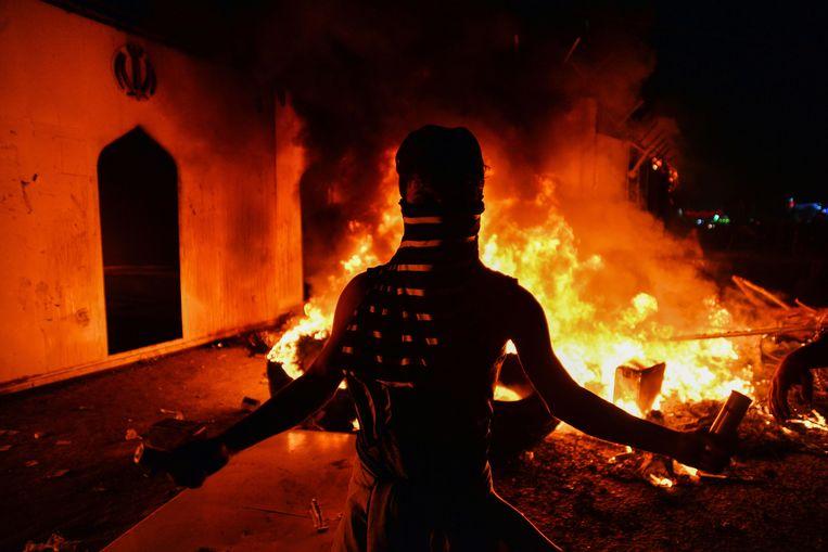 Demonstranten verzamelden zich woensdag bij de smeulende resten van het Iraanse consulaat in de stad Najaf.  Beeld AFP