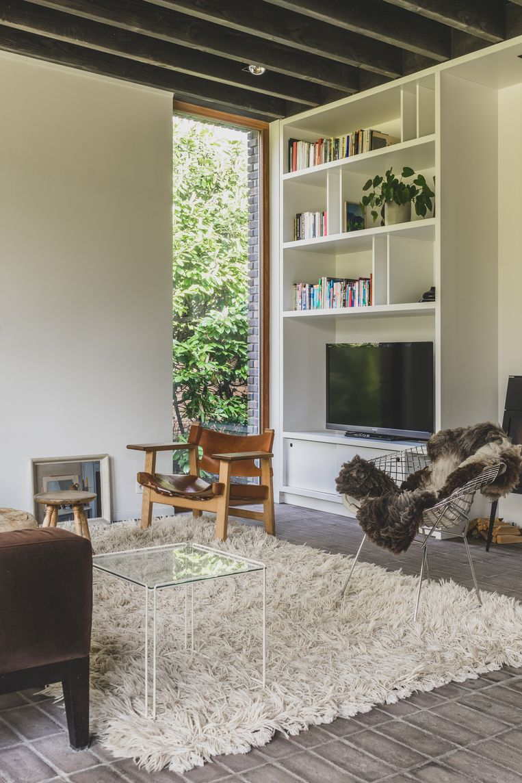 Typisch bij een woning van Eddy François is de bakstenen vloer. Met een wollig tapijt maak je die extra warm. De meubels zijn vintage.  Beeld Hannelore Veelaert