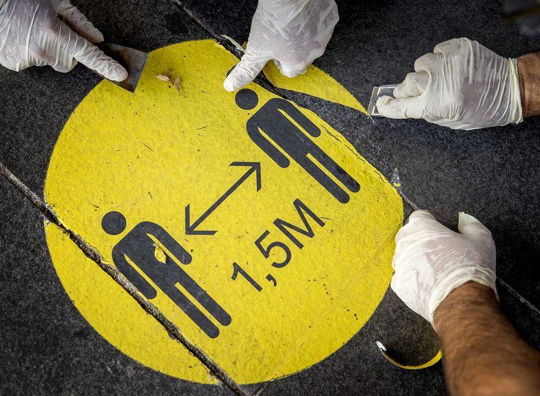 Medewerkers verwijderen stickers voor het Stedelijk Museum Amsterdam. op 24 september. Doordat de anderhalvemeterregel vervalt, hoeven bezoekers zich hier niet meer aan te houden.  Beeld ANP