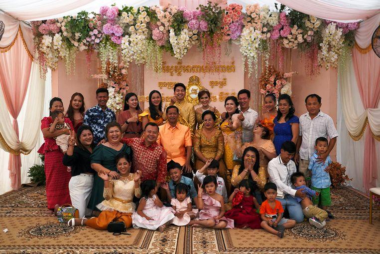 Met een groot gezelschap, dicht op elkaar, lachend op de foto. Mag dat wel? In Cambodja kan het weer nu de coronaregels daar onlangs zijn versoepeld. Deze traditionele bruiloftsceremonie in de hoofdstad Phnom Penh kon daarom na maanden uitstel alsnog doorgaan. Beeld Reuters