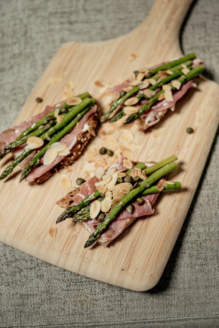 Tostadas met jamón serrano, groene asperges, olijven en kappertjes. Beeld Jakob van Vliet