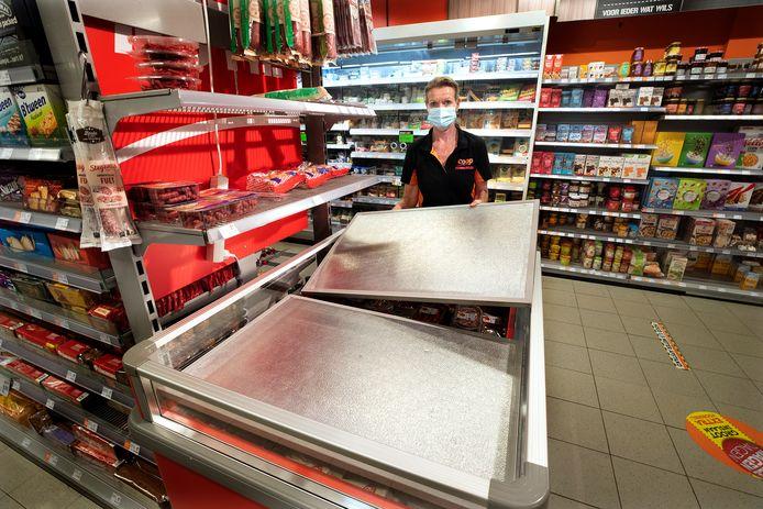 Supermarkteigenaar  Vera Leenders legt platen over de koelingen  tijdens de stroomstoring.
