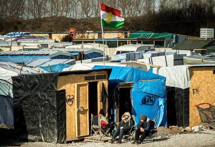 Asielzoekers zitten voor hun geïmproviseerde woning in de 'Jungle' van Calais.