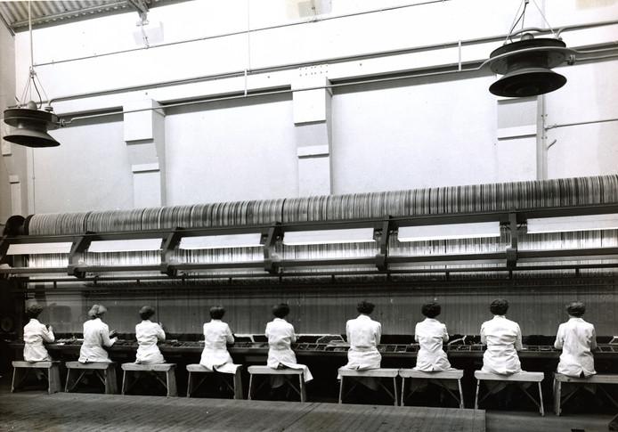 De handknoperij van Bergoss in 1956, waar druk wordt gewerkt aan een tapijt voor het Tuschinski Theater in Amsterdam.