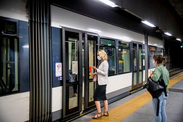 Mensen stappen met mondkapjes op en met acht voor social distancing in een tram in Gent. Archiefbeeld.