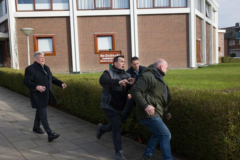 Een beveiliger van de NOS (in groene jas) met kerkgangers bij de Mieraskerk in Krimpen aan den IJssel. Vlak daarvoor was een journalist van RTV Rijnmond in zijn buik geschopt. Beeld Arie Kievit
