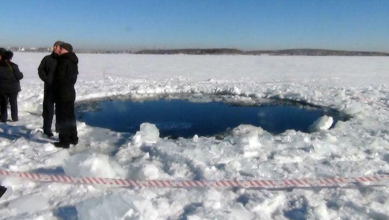 Mannen naast het gat (met een doorsnee van zes meter) dat door de asteroïde in het ijs is geslagen. Beeld afp