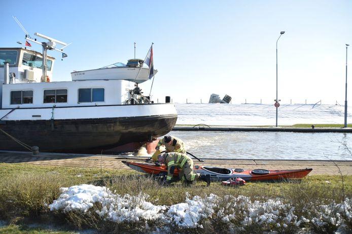 Hulpdiensten bij de omgeslagen kano nabij Doorwerth. Twee slachtoffers worden warm gehouden op een schip.
