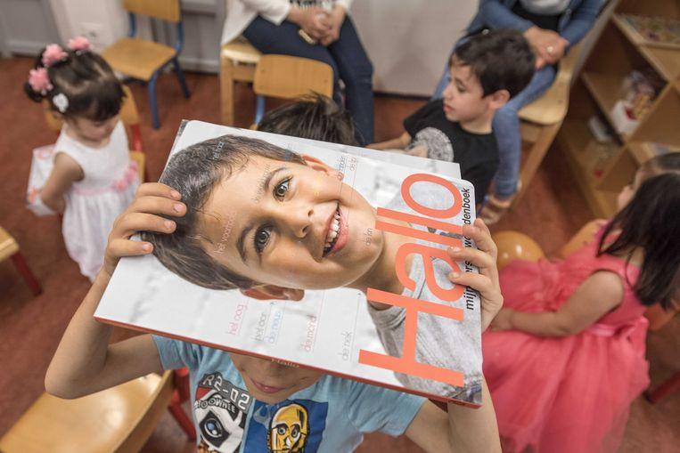 Kinderen die in asielzoekerscentra verblijven krijgen in 2017 het woordenboek Hallo uitgereikt. Met het woordenboek leren ze de eerste Nederlandse woorden die te maken hebben met het alledaagse leven.  Beeld ANP