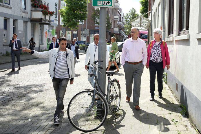 Burgemeester Aboutaleb loopt met enkele bewoners door de Tweebosbuurt. Rechts van de burgemeester wandelt An Rook. Achter de man met de witte jas en de zwarte jeans loopt bouwwethouder Bas Kurvers met buurtbewoner Ahmed Abdillahi.