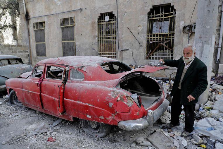 Mohammad Mohiedin Anis bij een van zijn vernielde wagens.  Beeld AFP